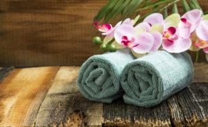 Spa Stilleben mit Orchideenblüten und weiche Handtücher auf Holzuntergrund