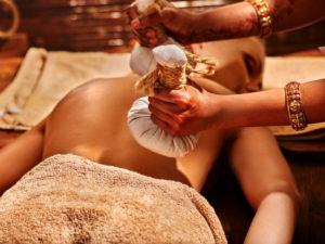 Frau mit ayurvedischer Massage mit Rückenbeutel aus Reis. Nahaufnahme von exotischen Indien-Massage.